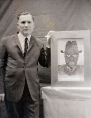 Albert K. Bender posing with a sketch of an MIB.